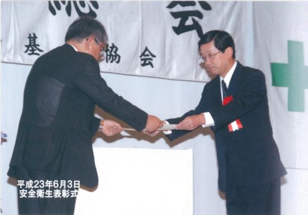 八幡労働基準協会清水会長より表彰されるNSES岡崎部長
